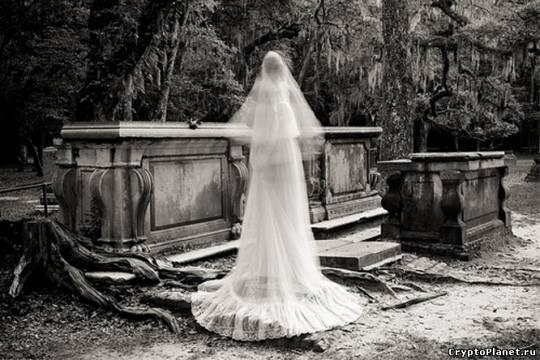 Женщина в белом парит на кладбище